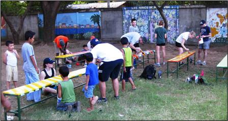 Bucknell students                                                   and kids painting                                                   benches