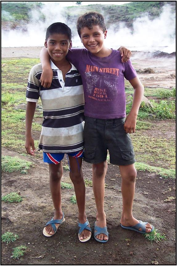 two boys in                                                   chinela shoes at the                                                   city dump